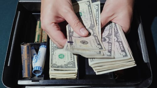 A Man Counts the Money in a Cash Box. Outbound Trade and Good Revenue Concept