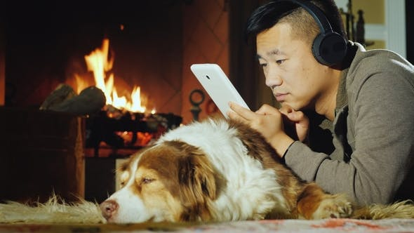 Cover Image for A Concentrated Asian Man Reads News on the Tablet. Lies Near the Fireplace with His Dog