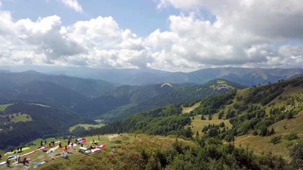 Thumbnail for Aerial View of Paragliding Takeoff with Flying Paraglide Pilots in Mountains Landscape