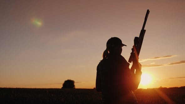 Thumbnail for A Woman with a Gun Goes Across the Field. The Beginning of the Hunting Season. Rear View