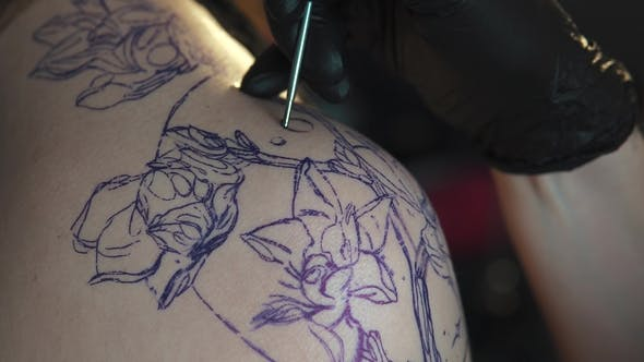 Thumbnail for Drawing a Tattoo on the Shoulder . Master Tattoo Makes a Rotary Tattoo Machine Gun