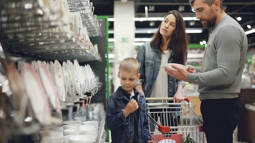 Smiling Family Is Buying Bowls and Plates in Kitchenware Department in Hypermarket, They Are Taking