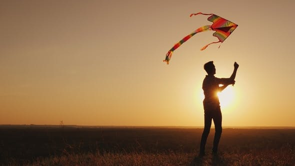 A Teenager Launches a Kite at Sunset.