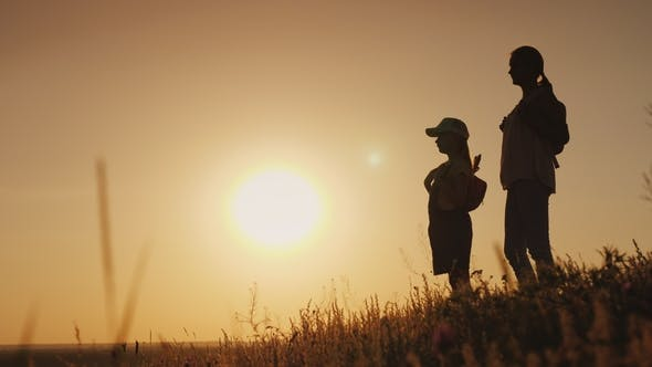 Thumbnail for Mom and Daughter Are Admiring the Sunrise. They Stand with Backpacks Behind Their Backs in a