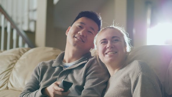 Cover Image for Morning Watching TV Together. Young Couple Sitting on the Couch, Having a Good Time Together