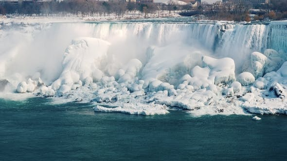 Thumbnail for The Frozen Niagara Falls. Streams of Water Fall on Rocks Covered with Ice. Nature USA and Canada in
