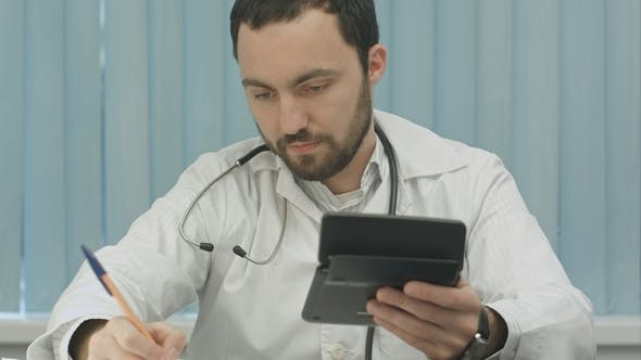 Thumbnail for Young  Male Doctor with a Calculator Make Calculations and Make Notes