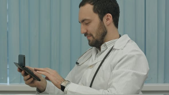 Bearded Doctor with a Calculator. Make Calculations of Price and Satisfied of It