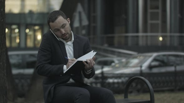 Thumbnail for Young Bearded Businessman Talking By Phone and Writing in Diary, Working with Notes at Green Park