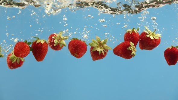Cover Image for Ripe Strawberries Fall Into Water on Blue Background. Summer Berry in Liquid