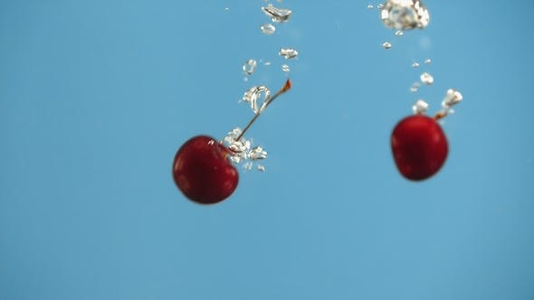 Cover Image for Two Cherry Berries Cherries Fall Into Water on Blue Background