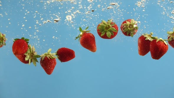 Thumbnail for Fresh Strawberry Fall Into Water on Blue Background. Summer Berries in Liquid