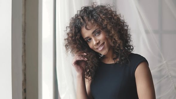 Thumbnail for Portrait of a Charming Hispanic Girl in a Black Dress. Curly Brown Girl