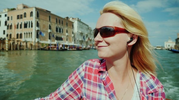 Cover Image for Holidays in Venice. A Woman Admires the Views of the City, Puffs on a Water Taxi
