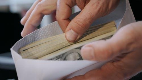 Cash Money in Envelope in Hands. Money Bonus in Paper Envelope