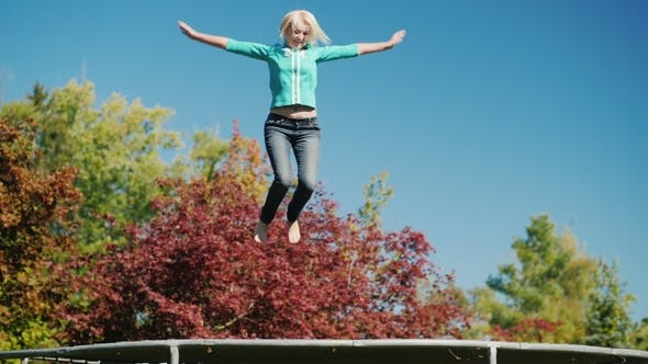 Cover Image for Active Lifestyle. A Middle-aged Woman Jumps High on a Trampoline. Against the Sky