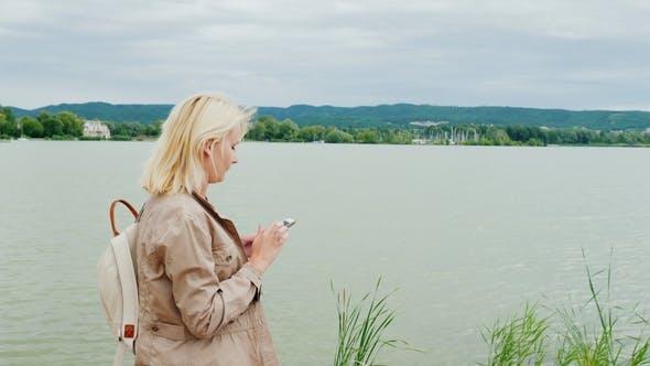 Thumbnail for Woman Is Walking Around the Lake, Using a Mobile Phone. Lake Balaton in Hungary. Steadicam Shot