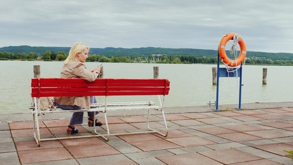 Thumbnail for Young Woman Sits on a Bench on the Background of a Large Lake. Uses a Mobile Phone. Lake Balaton in