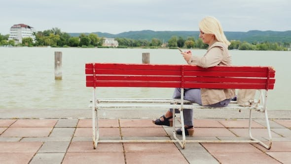 Cover Image for Woman Sits on a Bench on the Background of a Large Lake. Uses a Mobile Phone. Lake Balaton in