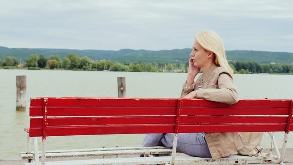 Cover Image for Woman Sits on a Bench on the Background of a Large Lake