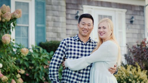 Portrait of a Happy Family on the Threshold of Their House. Asian Man and Caucasian Woman Hugging