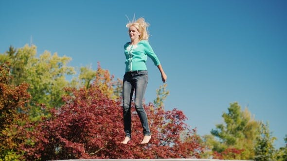 Thumbnail for A Middle Aged Woman High Up on a Trampoline