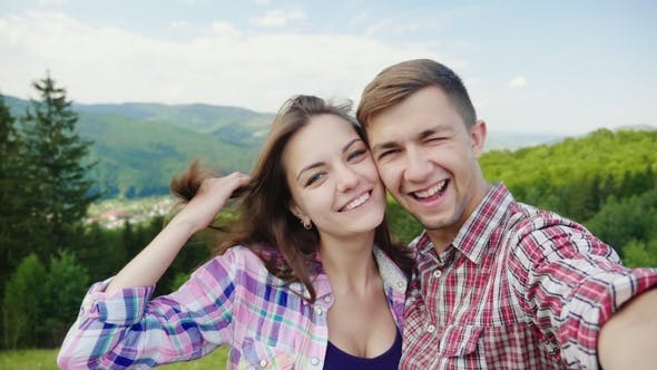 Thumbnail for Happy Couple Doing Selfie on a Background of Beautiful Mountains. Magnificent Vacation and Vacation