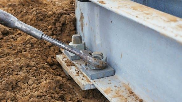 Thumbnail for Worker Twists Schraube auf Metall-Turmstütze auf Boden