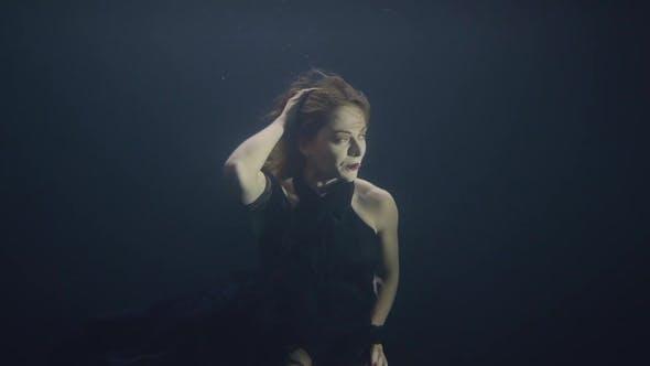 Attraktive Frau schwimmt unter Wasser im dunklen Pool während Video aufnahmen