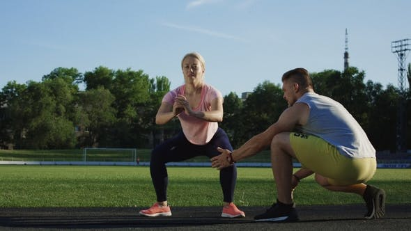 Thumbnail for Trainer Helping Woman with Squats on Field