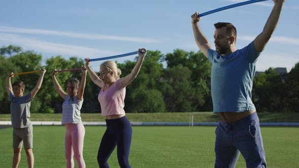 Thumbnail for Family Working Out with Personal Trainer on Field