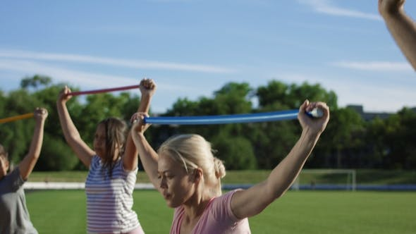 Woman with Kids Exercising on Sports Ground