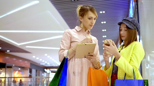 Thumbnail for Mother and Her Adult Daughter Using Tablet Computer for Planning Shopping in Mall