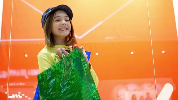 Thumbnail for Sale and Fashion Concept. Kid with Confident Face Expression and Casual Hairdo Does Shopping.