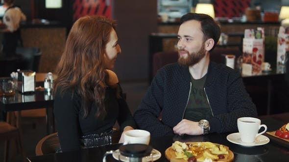 Thumbnail for Couple on a Date in a Restaurant. Young Guy and Girl Have Fun Talking While Sitting at a Table