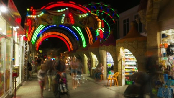 Thumbnail for Entrance in Amusement Park at Night, People Walk and Bay Souvenirs