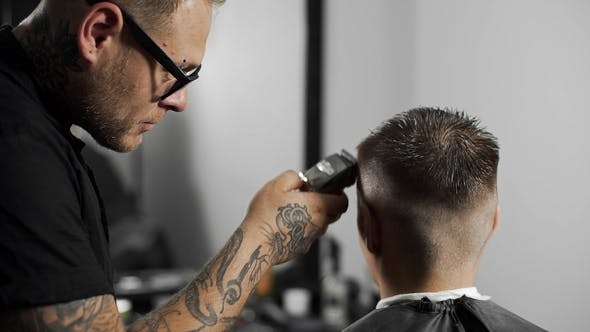 Thumbnail for Tattoed Barber Makes Haircut for Customer at the Barber Shop By Using Hairclipper, Man's Haircut and