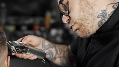 Tattoed Barber Makes Haircut for Customer at the Barber Shop