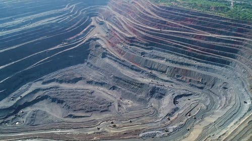 Aerial View of Opencast Mining Quarry with Lots of Machinery at Work.