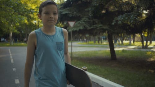 Skateboarder Walks in a Park with a Skateboard in Hands