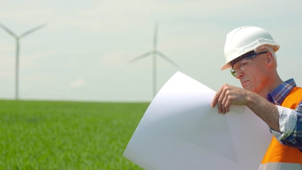 Thumbnail for Engineer Analyzing Plan While Looking At Windmills In Farm