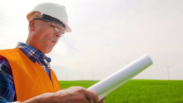 Thumbnail for Engineer Analyzing Plan While Standing In Windmill Farm