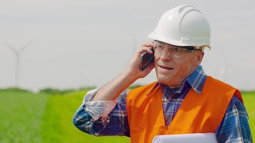 Engineer Talking On Mobile Phone While Walking In Farm
