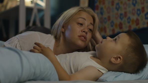 Woman Talking with Boy Before Falling Asleep