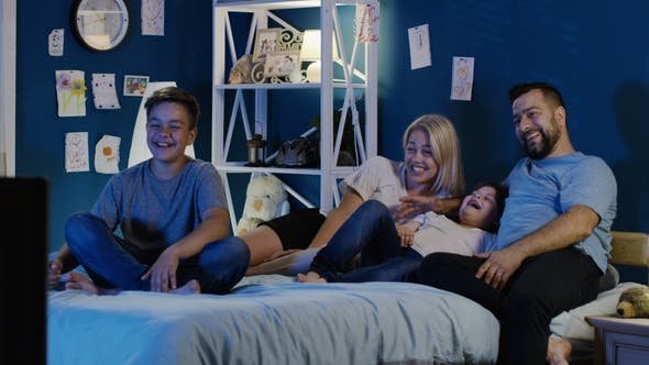 Thumbnail for Laughing Family Enjoying TV at Night