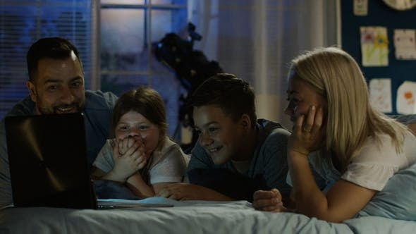 Thumbnail for Content Family Watching Funny Movie on Laptop
