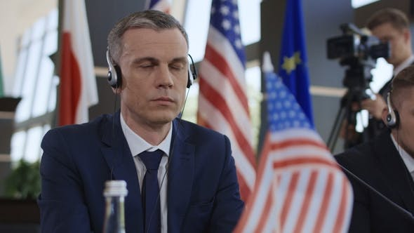 Thumbnail for Concentrated Politician Listening To Translation on Conference