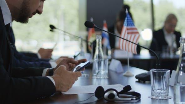 Thumbnail for Summit Member Using Phone at Table