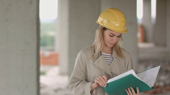Thumbnail for Young Female Architect Construction Engineer at a Construction Site Eximaining Documents