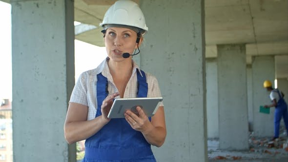 Female Construction Engineer Reading Plans Using Digital Tablet and Talk To Workers